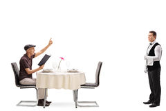 Elderly man calling a waiter. Elderly men sitting at a restaurant table and calling the waiter isolated on white background stock photo