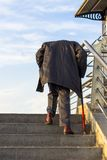 Elderly man with a cane climbing stairs stock image