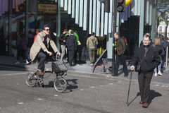 An elderly man with a cane cross the road, while the young man in fashionable coat riding a bicycle Stock Images