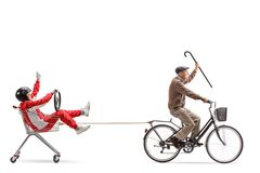 Elderly man with cane riding a bicycle and pulling a shopping ca. Elderly men with cane riding a bicycle and pulling a shopping cart with a men in a racing suit royalty free stock images