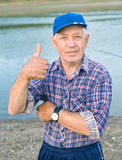 Elderly man in cap showing Tumbs Up Royalty Free Stock Photography