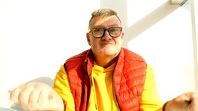 Elderly man of caucasian nationality, in bright clothes, fool around. Elderly man of caucasian nationality, in bright clothes, fool around, playing with a fork stock video footage