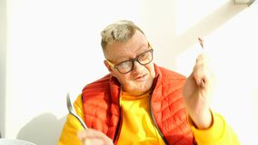 Elderly man of caucasian nationality, in bright clothes, fool around. Elderly man of caucasian nationality, in bright clothes, fool around, playing with a fork stock footage