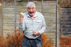 Elderly man celebrating his achievement . stock images