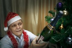 Elderly man, champagne, christmas fir stock photo