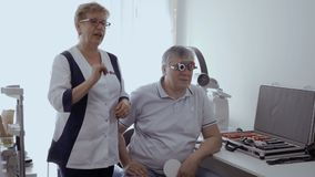 Elderly man check his eyesight with optical trial frame. Doctor check man`s sight with optical trial frame. Senior man has a bad eyesight and check it in stock video
