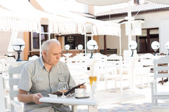 Elderly man checking his bill at a cafe Royalty Free Stock Photography