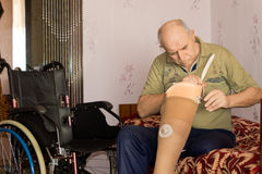 Elderly man checking out his artificial leg Stock Photos