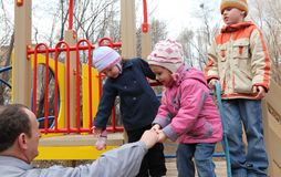 Elderly man with children on playground Stock Image