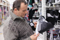 Elderly man chooses skates in sports shop Stock Images