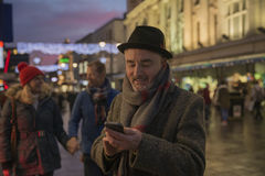 Elderly Man in City Centre on Mobile Device. Stock Photo