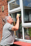 Elderly man washing or cleaning windows. Royalty Free Stock Images