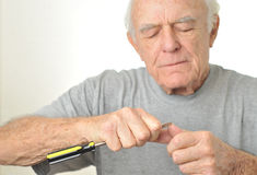 Elderly man cleans his fingernail with screwdriver Royalty Free Stock Photography