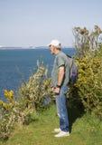 Elderly man on clifftop looking at ocean Stock Images