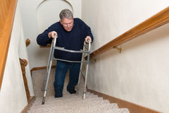 Elderly Man Climb Stairs, Walker. An elderly old senior man is having trouble climbing stairs with his medical aid walker. The stairway has him scared and stock image