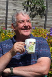 Elderly man close up drinking coffee outside. A close up of an elderly man sitting outside relaxing drinking a cup of coffee or tea in a garden Royalty Free Stock Photo