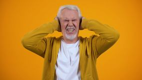 Elderly man closing ears by palms, irritated with gossips, orange background. Stock footage stock video footage