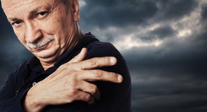 Elderly man on cloudy sky background Royalty Free Stock Photography