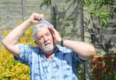 Elderly man combing his hair. Stock Images