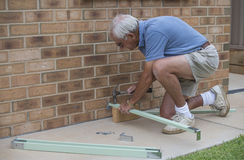 Elderly Man Hammering Nails And Wood. Stock Photography