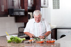 Elderly man cooking Stock Photo