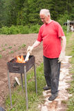 An elderly man cooks Stock Photos
