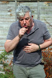 Elderly Man Coughing. Smoking. Royalty Free Stock Images