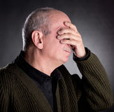 Elderly man covers his face with hand Royalty Free Stock Photos