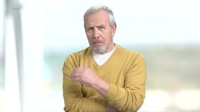 Elderly man with crossed arms. Senior man in casual sweater having sudden headache, blurred background stock video footage