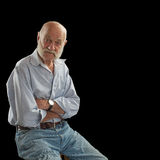Elderly man crosses arms and looks interested Stock Images