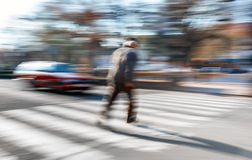 An elderly man crosses the street in a crosswalk Stock Photography