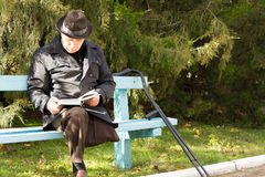 Elderly man on crutches sitting in the sun reading Royalty Free Stock Photography