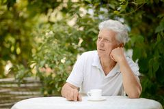Elderly man with cup of coffee. Elderly man  with cup of coffee at summer cafe Stock Images