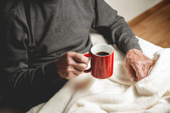 Elderly man with a cup of coffee. Elderly man sitting on the couch with a cup of coffee in hand Stock Photo