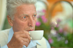 Elderly man with cup of coffee. Elderly man  with cup of coffee at summer cafe Stock Image