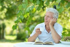 Elderly man with cup of coffee. Elderly man in a summer park with cup of coffee and book Stock Images