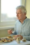 Elderly man with cup of tea Stock Images