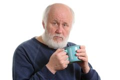 Elderly man with cup of tea or coffee isolated on white. Elderly grey haired man with blue cup of tea or coffe isolated on white royalty free stock photography