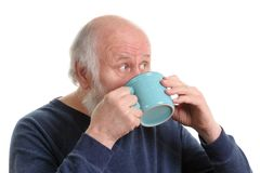 Elderly man with cup of tea or coffee isolated on white. Elderly grey haired man drikns from tea or coffee from blue cup isolated on white royalty free stock image