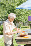 The elderly man cut vegetables for dinner Stock Photography