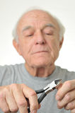 Elderly man cuts his fingernail with plyers Royalty Free Stock Photo