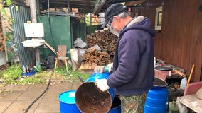 An elderly man cuts a metal barrel with a circular electric saw. Country life stock video