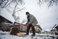 Elderly man cutting wood in winter. Breb, Romania - November 16, 2016: An elderly man slices wood logs on a winter day in Breb, Maramures, Romania Royalty Free Stock Images
