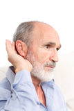 Elderly man with a deaf-aid. Picture taken from side of a man with a deaf-aid in his ear stock photo