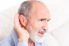 Elderly man with a deaf-aid. Picture taken from side of a man with a deaf-aid in his ear royalty free stock photos