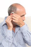 Elderly man with a deaf-aid. Senior puting a deaf-aid in his ear royalty free stock photography