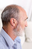 Elderly man with a deaf-aid. Side pic of a man with a deaf-aid in his ear royalty free stock photo