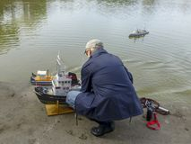 Elderly man descends a sailing model ship on the lake. Horizontal stock images