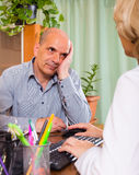 Elderly man with doctor in clinic Stock Image