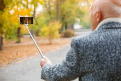 An elderly man does selfie on a mobile phone with a monopod. royalty free stock photo